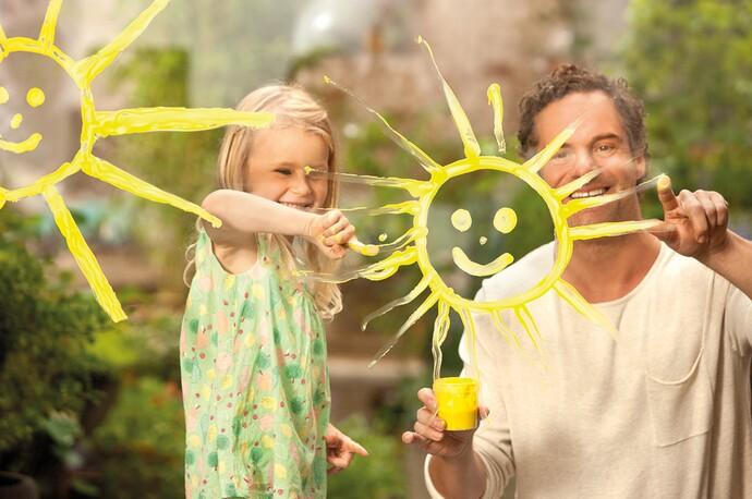 Otec a dcéra maľujú symbol vykurovania cez solárne systémy